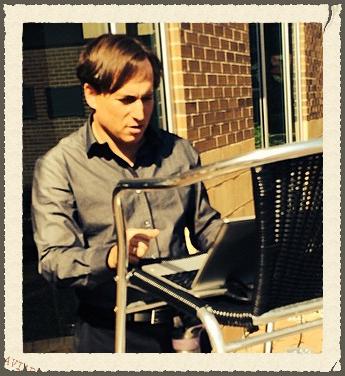"Shep Englander writing at makeshift ""standing desk"" in JCC courtyard."